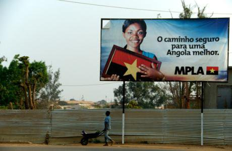 A boy with an empty wheelbarrow walks underneath an MPLA propaganda banner in the town of Menongue. Demotix. All rights reserved..jpg