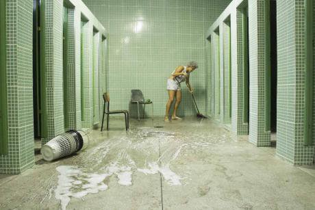 A female student mopping the floor of the school bathroom
