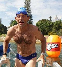 Hairy-chested man in swim cap and speedos exits a lake