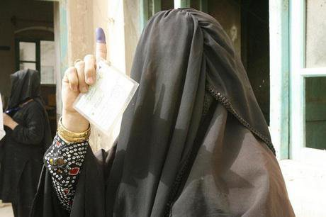 A burqa-clad woman shows her inky finger and her card after casting a vote at a polling station in Istalif, Sept 2010
