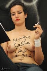 Dark-haired woman reclining with a book and cigarette, with Arabic words written on her bare chest.