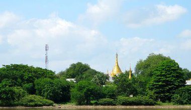 A mobile phone antenna and golden temple behind green trees alongside a river