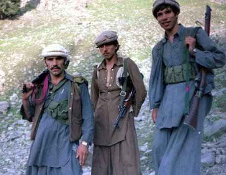 Afghan Mujahideen, dressed in traditional pashto clothing, pose with their rifles.