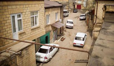 View of modern Derbent. Several cars are parked haphazardly on a cracked street.
