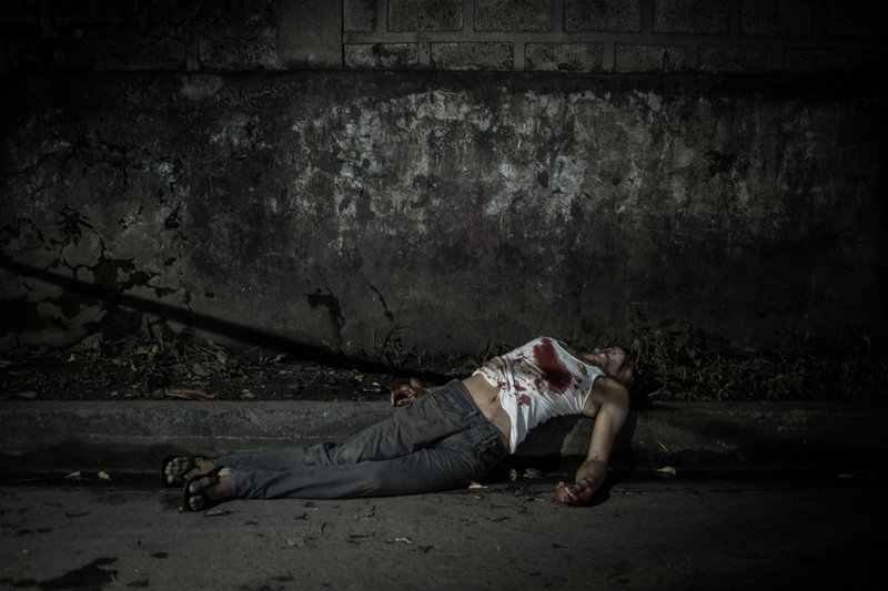 A bloodied lifeless body lies on a street.