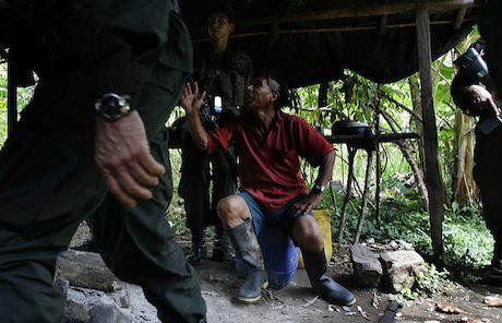 A coca farmer worker speaks with police, Colombia. Flickr / Policia Colombia. Some rights reserved.