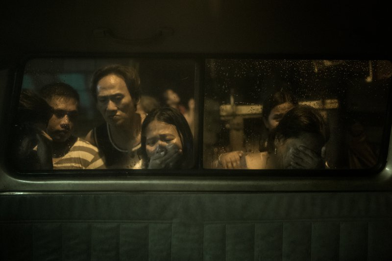 Dimly lit people looking through a window, one of them a woman crying.