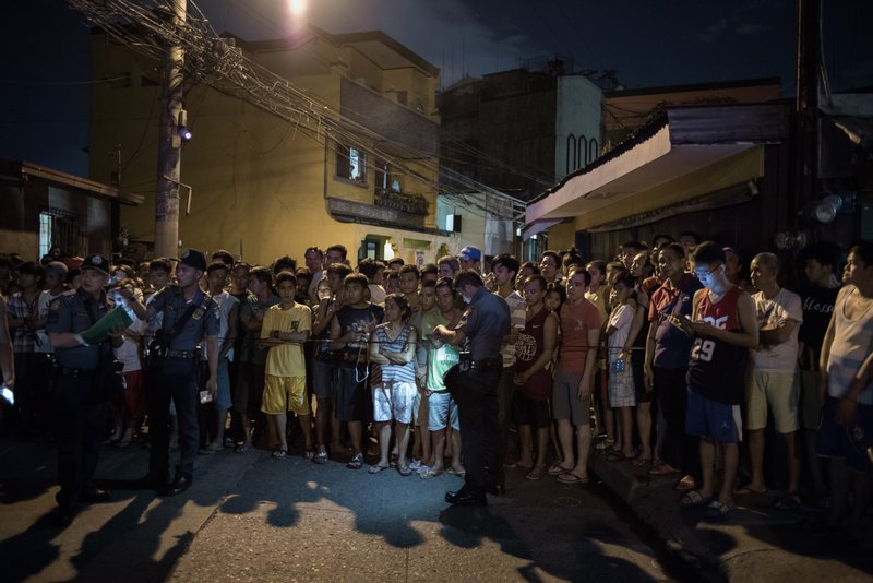 A crowd of people behind a police cordon at night in a city street.