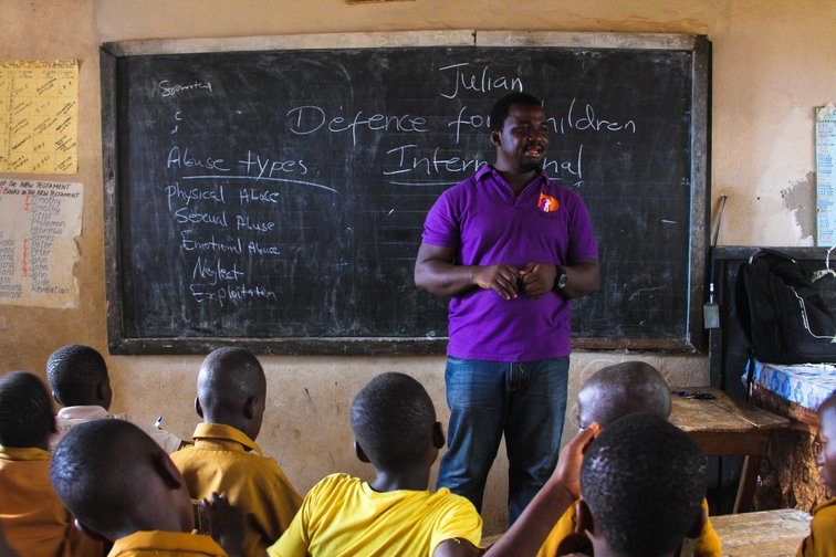 A man in front of a blackboard speaking to a class of children