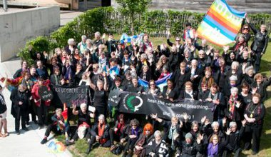 A hundred women, dressed in black, with banners and flags