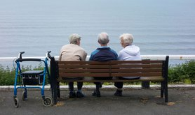 Two elderly men and an elderly woman sitting on bench overlooking sea. Saltburn by the Sea, North Yorkshire, England, UK