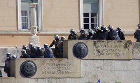 Greek riot police cascading down steps of a state building