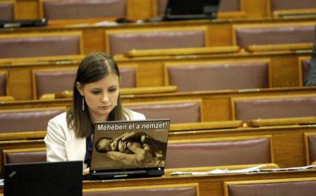 Far-right politician Duro Dora with laptop sticker 'the nation lives in its womb'. Credit - Magyar Narancs (1).jpg