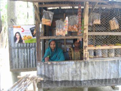 A women sitting in a corrugated iron shack surrounded by produce and items for sale