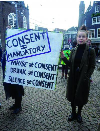 A member of the The Feminist Club Amsterdam holds a sign advocating for consent at the Amsterdam mini-rok protest. Jess Graham.