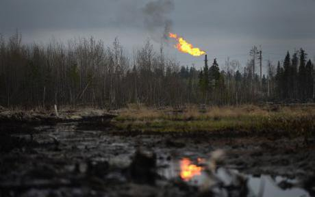 Crude oil seeps through the ground, in the background, a derrick burns off gas.