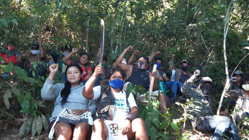 Guajajara Indians posing for a photo in Arariboia. During the coronavirus pandemic, almost all of them have been using facemasks during their treks through the forest. One of them, in the background, with a blue mask, shows the camera a bottle of antibacterial gel
