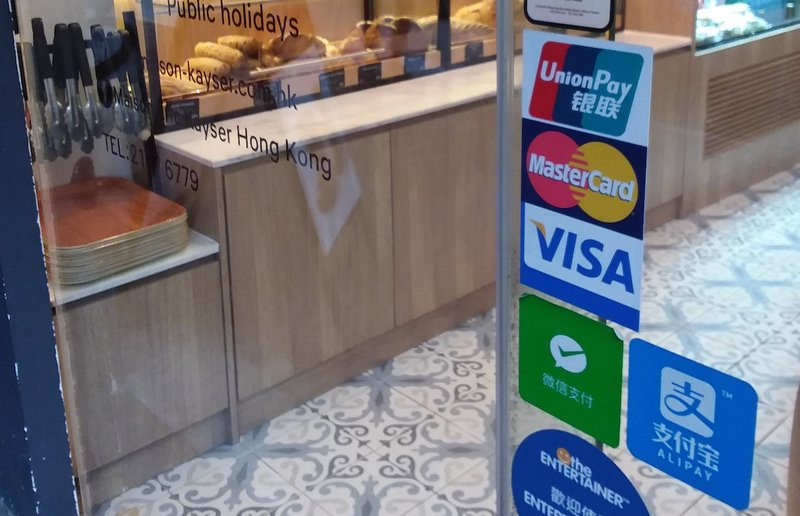 WeChat and AliPay stickers next to Visa and Mastercard on a bakery window illustrate the changing payments landscape.