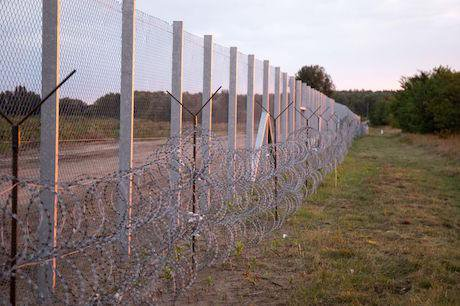 A long, tall wire fence with barbed wire running through a field.