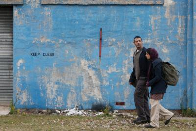 Man and woman walking side-by-side in front of blue wall