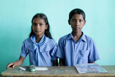 Bangladeshi schoolgirl and schoolboy sit side-by-side at a school desk: looking straight at the camera.