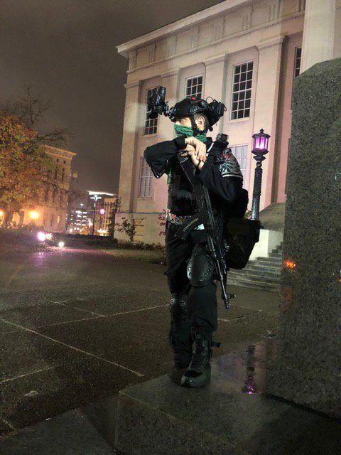 Masked White man with a rifle outside Louisville public library, protecting Black Lives Matter protestors, 29 October 2020