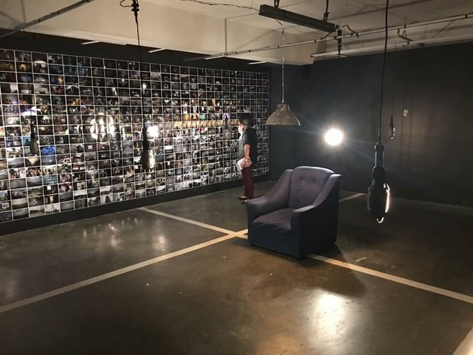 An armchair in a room whose walls are covered in photographs, with hanging lamps.