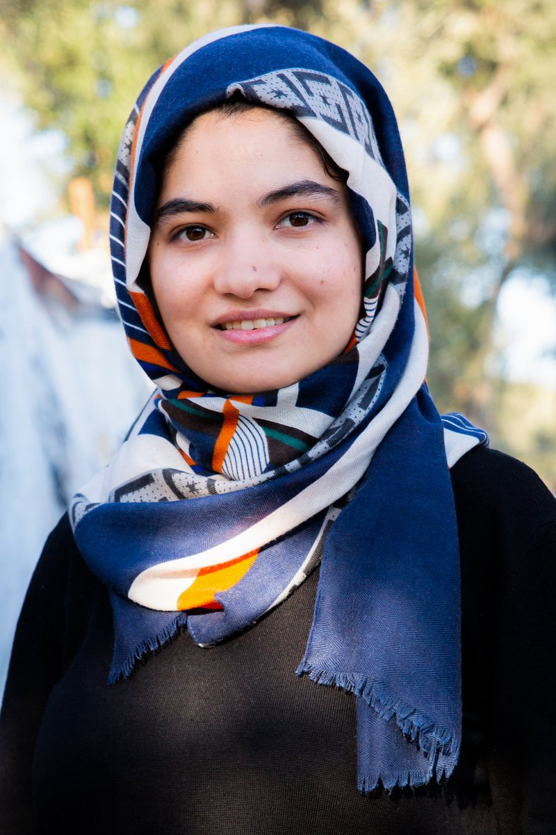 A portrait photo of a young Afghan woman in a headscarf