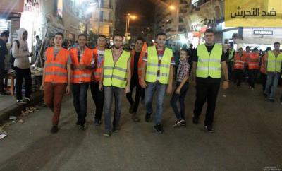 A group of 7 or so men in high-visibility vests walk down the middle of a street, stared at by on-lookers.