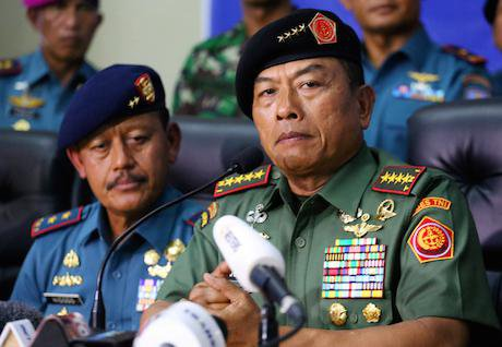 Indonesian military commander sits in front of a microphone.