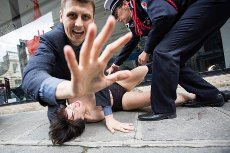 FEMEN activist is tackled to the ground.