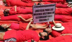 Women dressed in red lying down in a protest stunt
