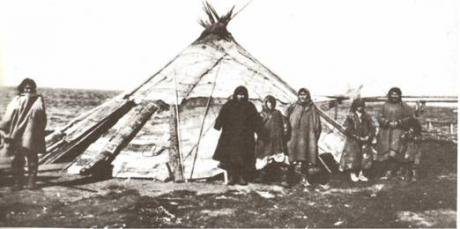 Black and white photo of a Khanty family in front of a 'chum' [traditional nomadic dwelling] in the early 20th century