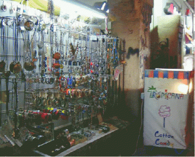 Street stall with jewelry on display and a 'Tropicana' sign