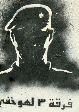 Grafitti stencil of a sinister face with Arabic script below