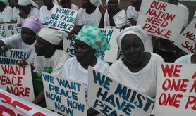 Liberian Women, all dressed in white, protesting with signs