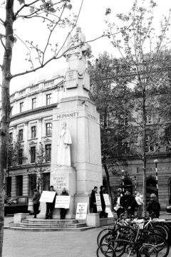 Black and white photo of women dressed in black with signs surrounding a monument