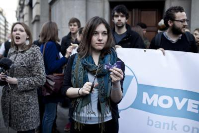 Women holds up a credit card and scissors, surrounded by campaigners