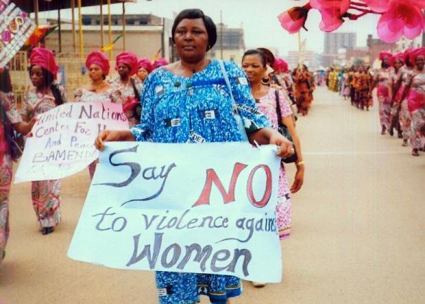 Women on a protest in Cameroon holding banners saying 'Say no to violence against women'
