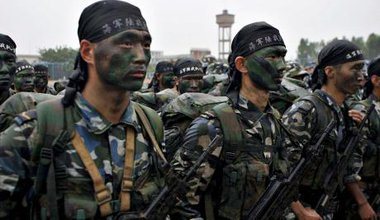 Chinese marines drill. They are armed and their faces are covered in war paint.