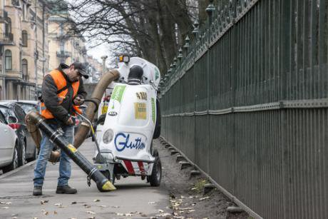Migrant worker cleaning the Tavricheskaya st., from the leaves, by big vacuum cleaner. Russia, Saint-Petersburg, Tavricheskay st. - Kalabi Yau - Shutterstock.jpg