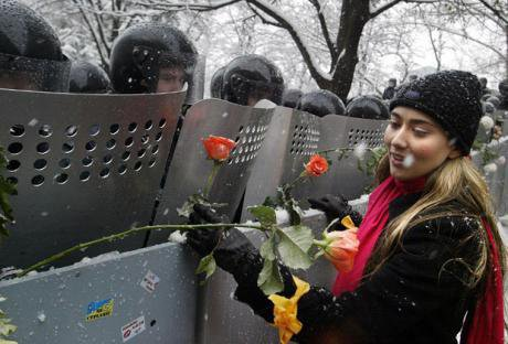 An Orange protester gives a flower to a uniformed riot police officer.