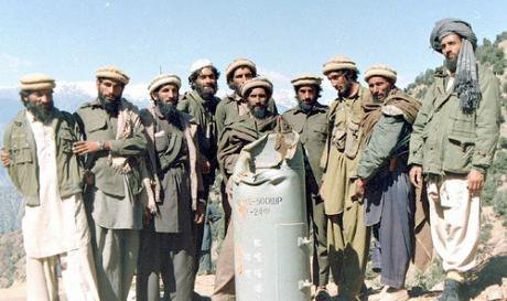 A group of armed mujahideen pose for the camera in front of a Soviet bomb case.