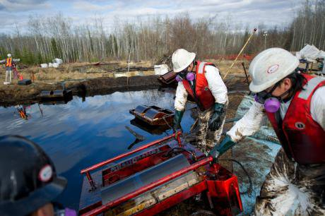 White-suited workers knee-deep in oil