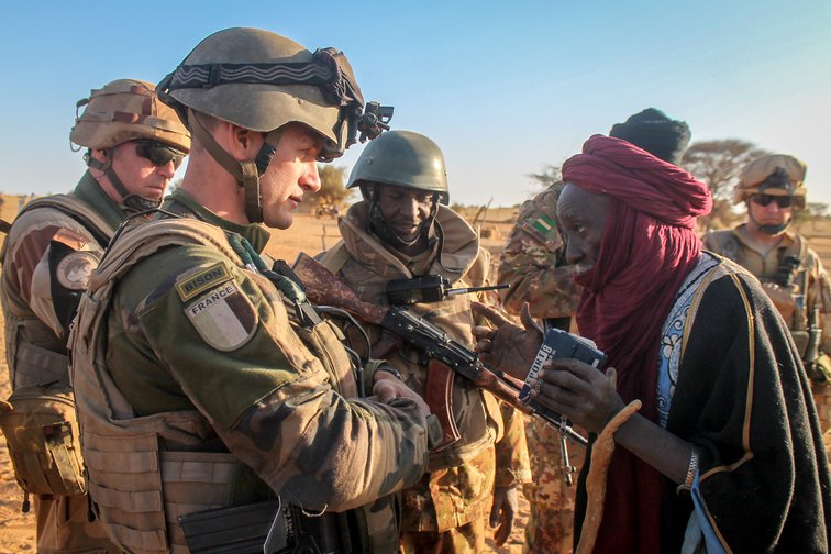 A French soldier, part of the Operation Barkhane taskforce, speaks to a man in Mali, 2016.