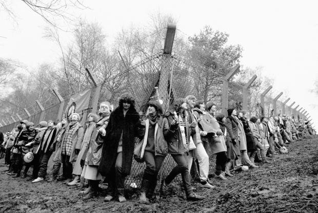 Black and white image of women surrounding RAF Greenham Common air base in a protest in 1982