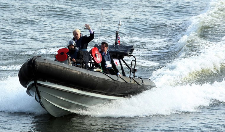Rigid inflatable boat speeding across the water, blond man standing on it with arm raised