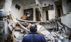 A civilian looks at a destroyed home in Aleppo, Syria. Andoni Lubaki/AP/Press Association Images. All rights reserved.