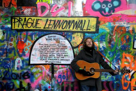 A musician at Prague's famous 'Lennon Wall' plays in support of democracy activists in Hong Kong. (AP Photo/Petr David Josek)