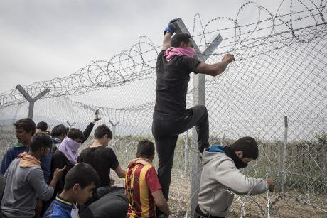 Men try to climb a fence at the Macedonia-Greece border in 2016.